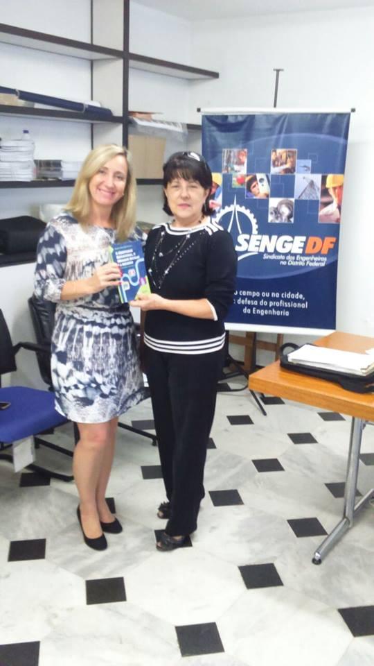 """Presidente da AOESC, Diléia Pereira Bez Fontana recebendo o livro """"O Orientador Educacional, o Mediador da Escolar e a Inclusão - Um caminho em construção"""" da autora e Presidente da ASFOE, Sra. Marise Miranda Gomes."""