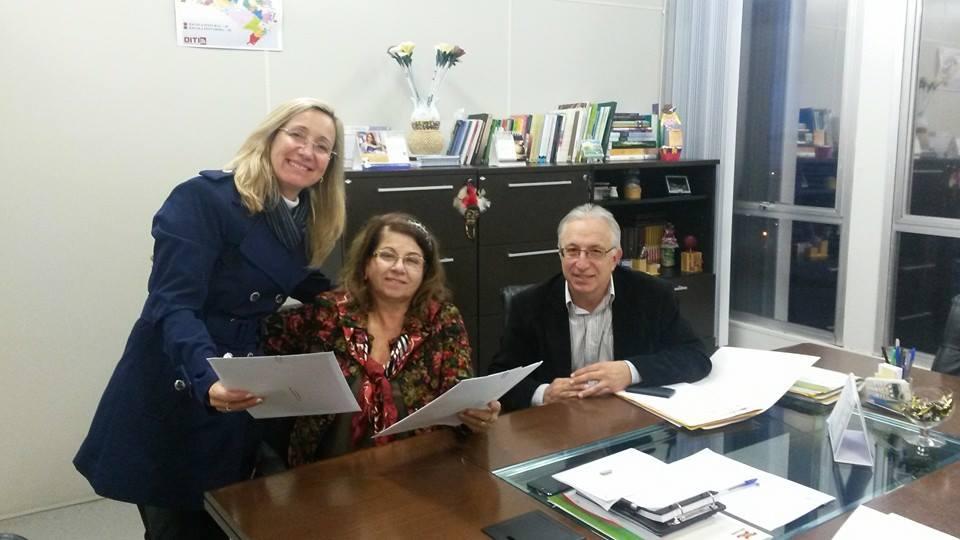 A Presidente da AOESC, Sra. Diléia Pereira Bez Fontana realiza a entrega do Projeto do XXIII Seminário a Secretária Adjunta da Educação do Estado de Santa Catarina, Profa. Elza Marina Moretto e seu respectivo Assessor Sr. Mário Tessari.