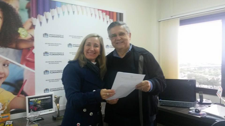 A Presidente da AOESC, Sra. Diléia Pereira Bez Fontana realiza a entrega do Projeto do XXIII Seminário ao Secretário Municipal de Educação de Florianópolis, Prof. Rodolfo Joaquim Pinto da Luz.
